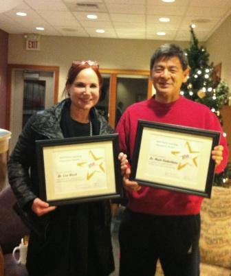 Dr. Lisa Block and Dr. Mark Kadoshima holding awards given by First 5 FUNdamentals for their work as early learning champions.